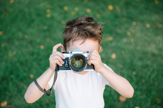 funny cute kid wants to take a picture with his vintage film camera