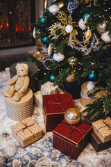 Vertical picture of decorated Christmas tree with balls and many presents under fir tree. Pleasant moments and festive event. Composition of pile with gifts. New Year`s holidays.