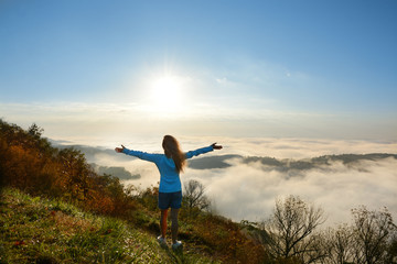 Girl standing on a top of the mountain at sunrise with her  hands up looking at beautiful foggy mountain landscape during her hiking trip. Near Blowing Rock, Blue Ridge Mountains, North Carolina, USA.