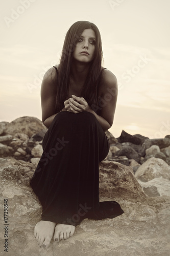 sad woman crying sitting on rocks fotolia com の ストック写真と