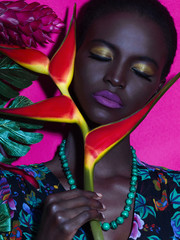 Dark-skinned girl with an exotic flower