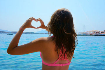 girl on the beach, hands in the shape of the heart