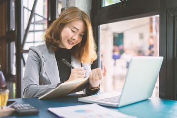 Asian Business woman working in office with documents writing business plan or make a list of product,education or technology or startup business concept, modern office or living room with copy space