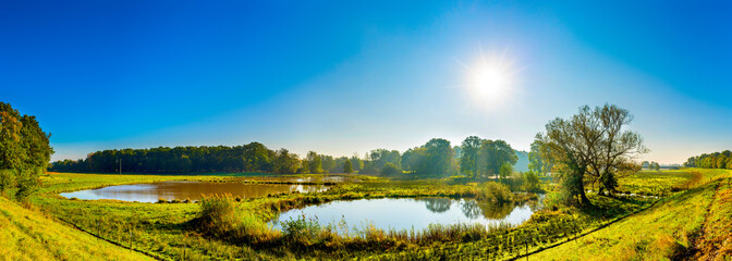 Beautiful landscape with ponds, meadows and bright sun
