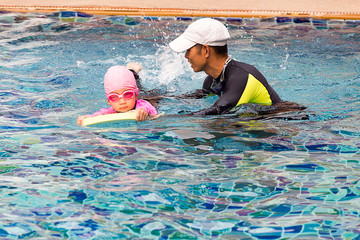 Cute little girl learning to swim with father