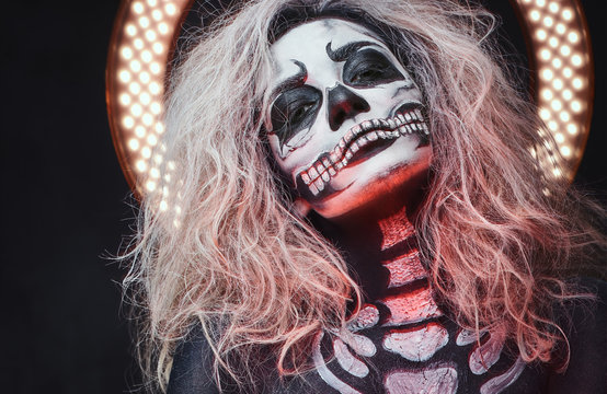 Halloween female skull makeup with creative lightening.