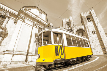 Historic tram line in front of Lisbon Cathedral in Alfama district, Lisbon, Portugal. Lisbon street with typical yellow vintage tram and Se de Lisboa in sepia monochrome background.