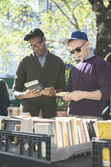 Young Gay Men Friends Browsing at Outdoor Used Books Sale at Manhattan's Central Park in New York