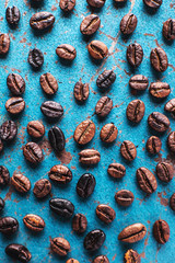 Roasted coffee beans on blue background.