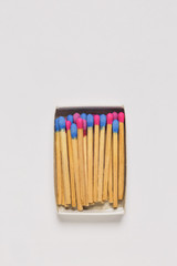 Red and blue wooden matches in a match box on white