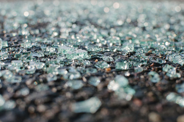 Close-up of shattered windshield glass on pavement