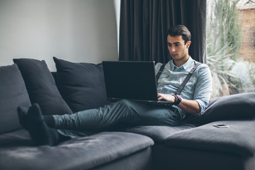 Man Working on a Laptop in the Living Room