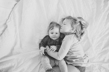 Cute, happy toddler girl kissing baby sister lying down on soft white bed