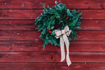 christmas wreath on a red barn wall