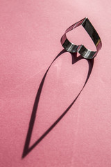 Heart shaped cookie cutter casts a long shadow on a pink background