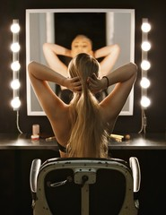 Beautiful model styling her hair in the mirror