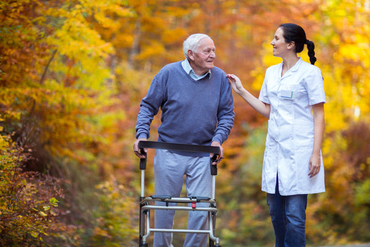 Nurse helping elderly senior man. Senior man using a walker with caregiver outdoor