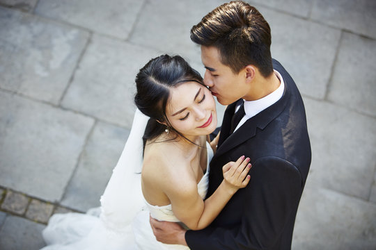 young asian bride and groom dancing in open air