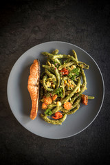 Salmon and spinach spaghetti in the plate on dark background