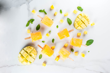 Ice cream, popsicles. Organic dietary foods, desserts. Frozen mango smoothie, with mint leaves and fresh mango fruit, on a white marble table. Copy space top view
