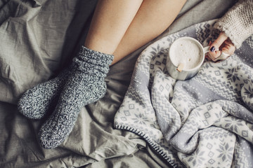 Woman In Woolen Socks Drinking Hot Coffee in Bed in the Morning