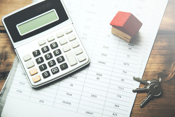 house model with calculator and key on document