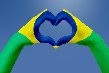 Garden Poster Brazil Hands flag of Brazil, shape a heart. Concept of country symbol, on blue sky.