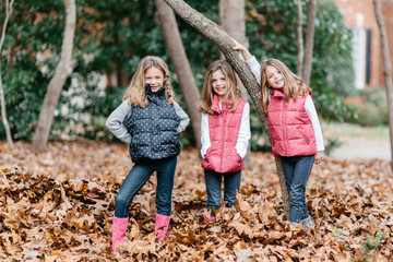 Cute young girls standing in a bed of leaves