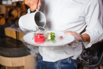 Hands chef holding a white plate with ice cream dessert and pouring from the jug with dry