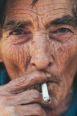 Old woman smoking closeup