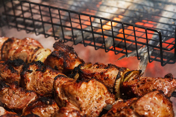 Fried juicy bbq meat and fish in a grill on a fire cooking food on a bonfire