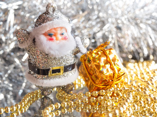 Small toy Santa Claus with gifts on a brilliant bright silver background. Toned.