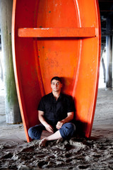 Man sitting under Santa Monica Pier under an orange boat.