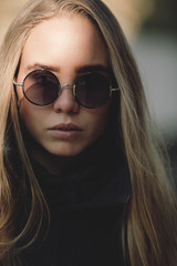 portrait of blond woman with round sunglasses in closeup