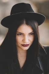 young woman with black hat and red-wine color lips