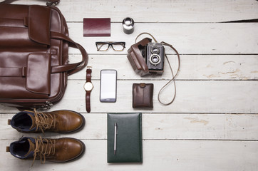 Still life with Men's casual outfits with leather accessories on brown wooden background, beauty and fashion, travel concept