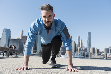 Handsome caucasian male crouched down in running position with New York City skyline