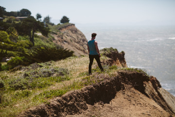 Strong brunette man stands overlooking the pacific ocean on a cliff