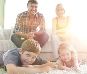 Portrait of happy family sitting together in living room