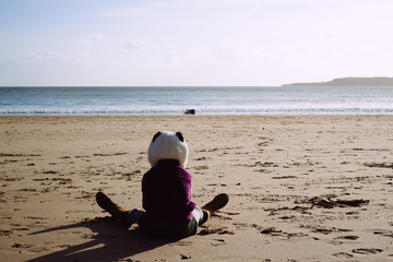 A little girl in a panda hat sitting on a beach looking at the sea.