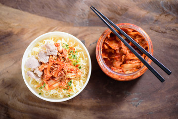 Korean food,instant noodle with kimchi cabbage in a bowl on wooden background.Top view of food