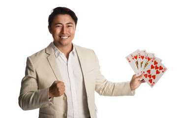 Laughing man wearing a beige suit holding a fan of cards in his hands showing a royal flush. White background.