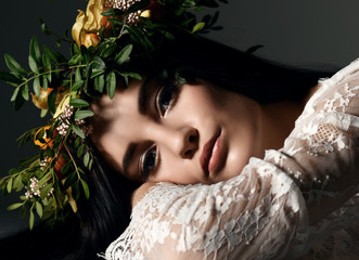 Beautiful portrait of young woman with wreath of flowers lying on a floor
