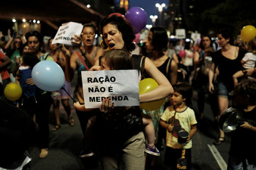 """Woman holds her baby as holding a sign reading """"Food Pellets are not meal"""" during a protest against Sao Paulo Mayor Doria's plans to serve school meals made of reprocessed food pellets in Sao Paulo"""