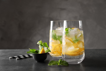 Glasses of cocktail with mint and lemon on grey background