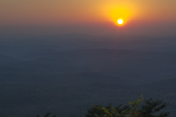 The sun prepares to dip below the horizon beyond the valleys visible from Cheaha State Park in Alabama, USA