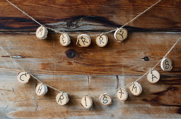 Close up of Merry Christmas letters on birch discs hanging from jute string