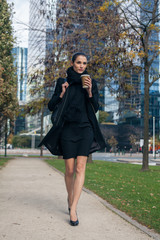 Pretty Woman Walking Down the Street and Holding Coffee Cup