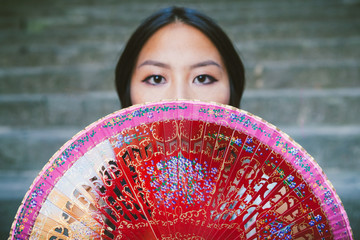 Young Asian Woman Hiding behind a Traditional Chinese Fan