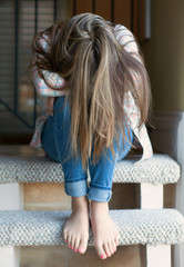 Teenage girl with long hair - head down hiding her face
